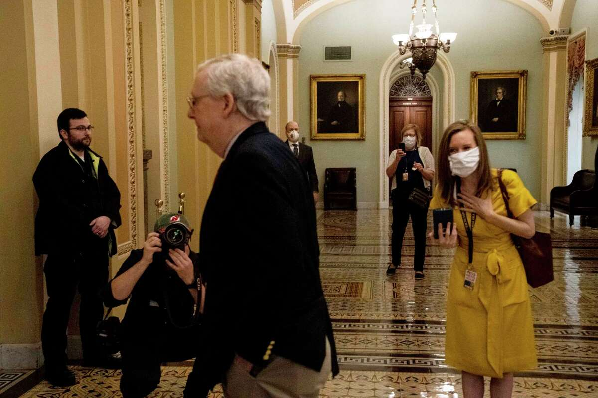 Senate staffers and reporters are seen wearing masks as Senate Majority Leader Sen. Mitch McConnell (R-Ky.) walks to the Senate floor at the Capitol in Washington, Thursday, April 9, 2020. A $250 billion package to replenish a small business loan program created by the coronavirus stimulus law has stalled in the Senate after Republicans and Democrats clashed over what should be included. (Anna Moneymaker/The New York Times)