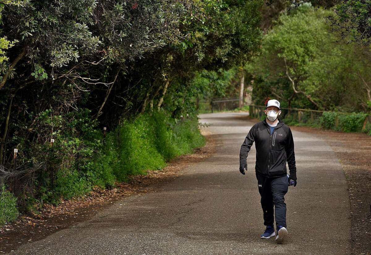 Jordan Frease, who had quadruple bypass surgery 8 months ago, walks along the Mountain Lake Trail in the Presidio in San Francisco, Calif., on Wednesday, April 8, 2020. Jordan lives alone, and is forced into further isolation as measures to prevent the spread of Covid-19 have removed him from most contact except for his required cardio walks.