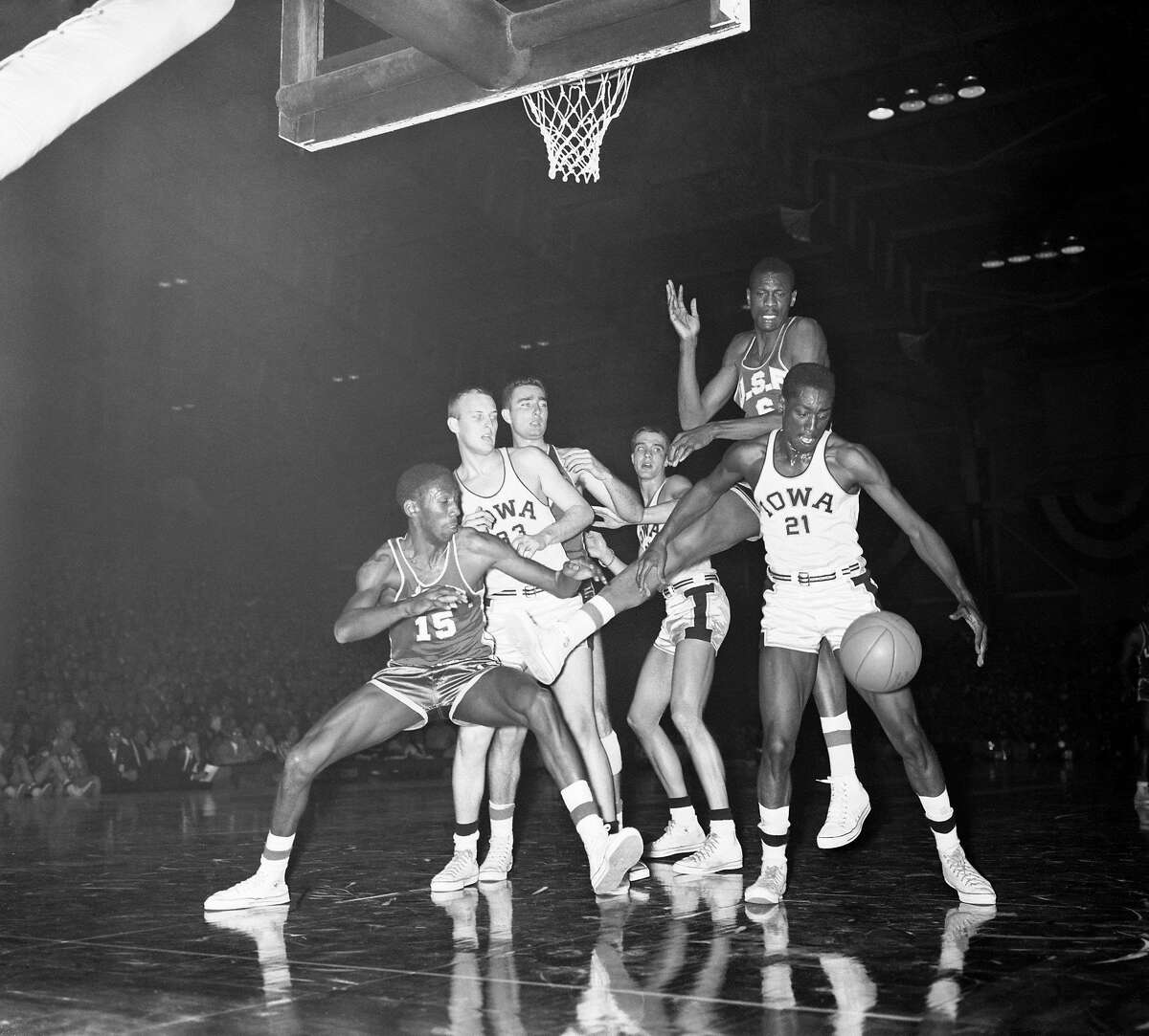 Iowa Hawkeyes and San Francisco Dons have varied expressions as they watch the ball fly loose during tussle under the basket in the first half of their title game in the NCAA tournament on March 23, 1956 in Evanston, Illinois. L to R: Gene Brown, Bill Schoof, Mike Farmer, Bill Logan, Bill Russell, and Carl Cain.