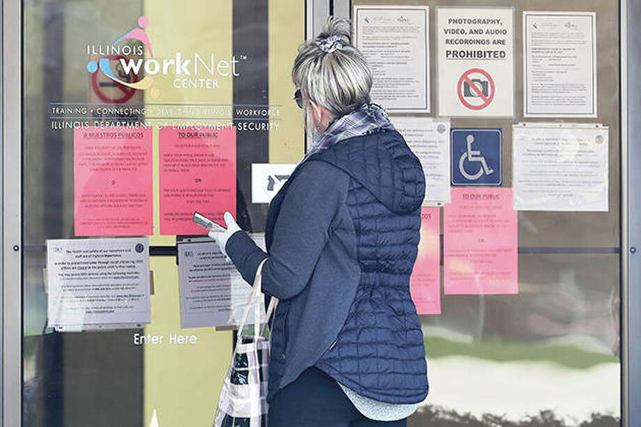 A woman checks job application information in front of an Illinois Department of Employment Security center. Another 6.6 million people filed for unemployment benefits last week, according to the U.S. Department of Labor, as American workers continue to suffer from devastating job losses, furloughs and reduced hours during the coronavirus pandemic. Photo: Nam Y. Huh | AP
