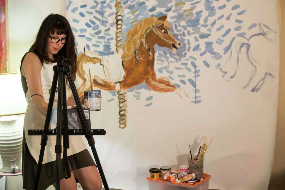 Artist Elena Sandovici interacts with her followers on social media as she works in her at-home art studio on Sunday, March 29, 2020 in Houston. To relieve boredom and connect with her art patrons, Sandovici started doing something she'd never done before: painting live on Facebook live. One of her paintings sold before it was even finished. Photo: Brett Coomer / Staff Photographer / © 2020 Houston Chronicle