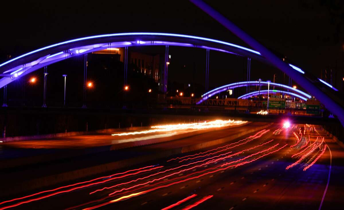 Traffic moves along I59 under blue lighted bridges shown from the Dunlavy bridge Thursday, April 9, 2020. Various Houston venues were lit blue as part of a nationwide #LightItBlue movement to honor essential workers on the front lines of the coronavirus pandemic.