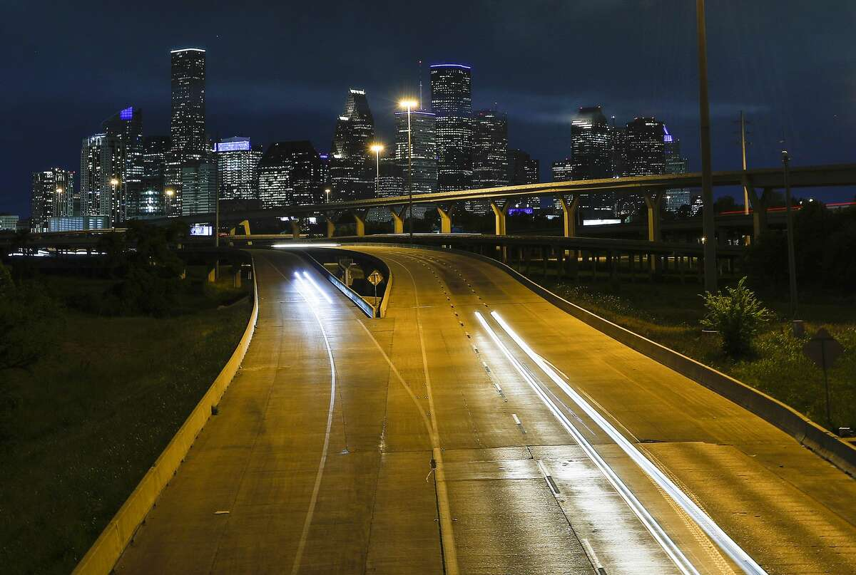 The downtown skyline, with several buildings lit in blue lights, looking south on I-45 North in Houston, Thursday, April 9, 2020.