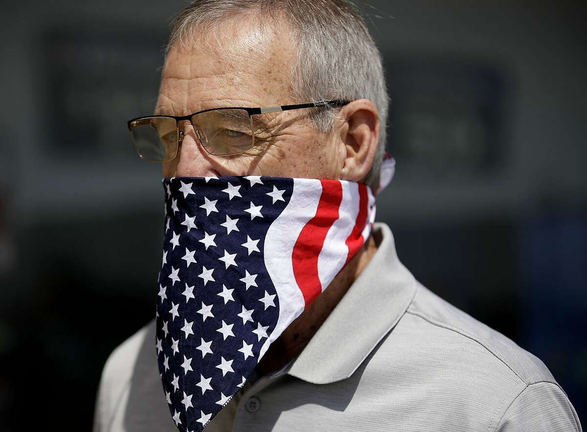 Larry Young of Collinsville wears an American flag bandana while shopping in Owasso ,Tuesday, April 7, 2020. (Mike Simons/Tulsa World via AP)