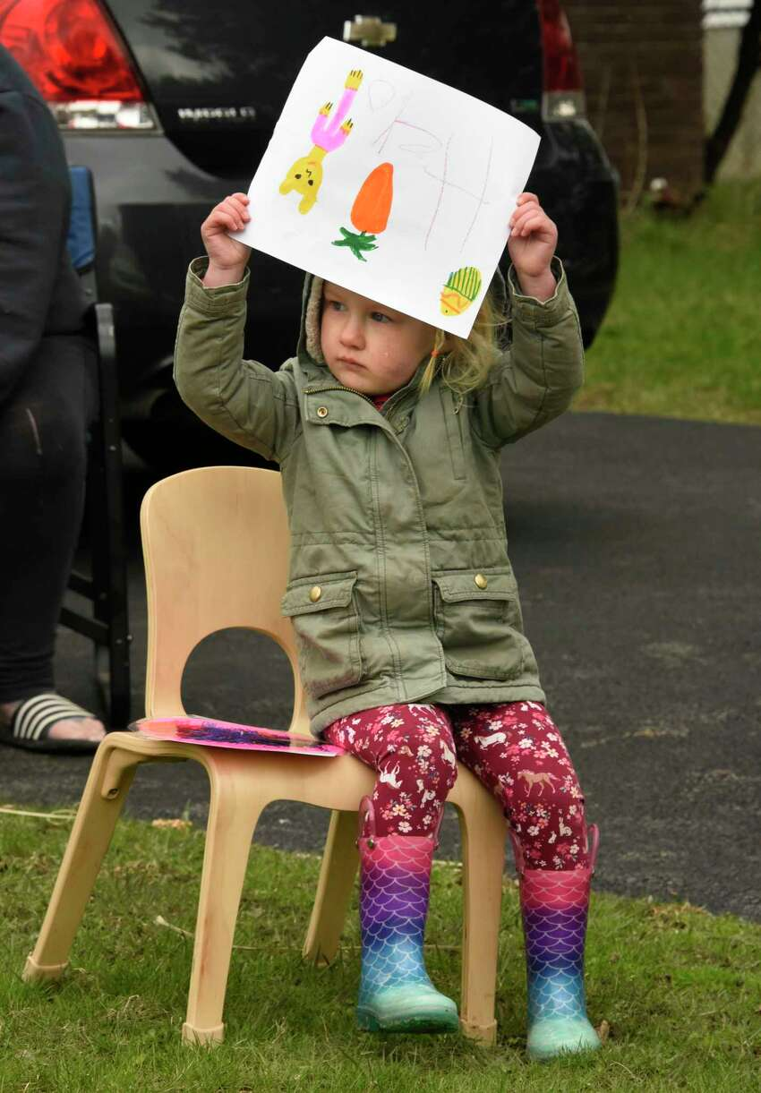 Kenley O'Connor, 2 1/2, along with other children from the Koala-T Daycare watch as the Easter Bunny rides on a firetruck through East Greenbush neighborhoods on Friday, April 10, 2020 in East Greenbush, N.Y. (Lori Van Buren/Times Union)