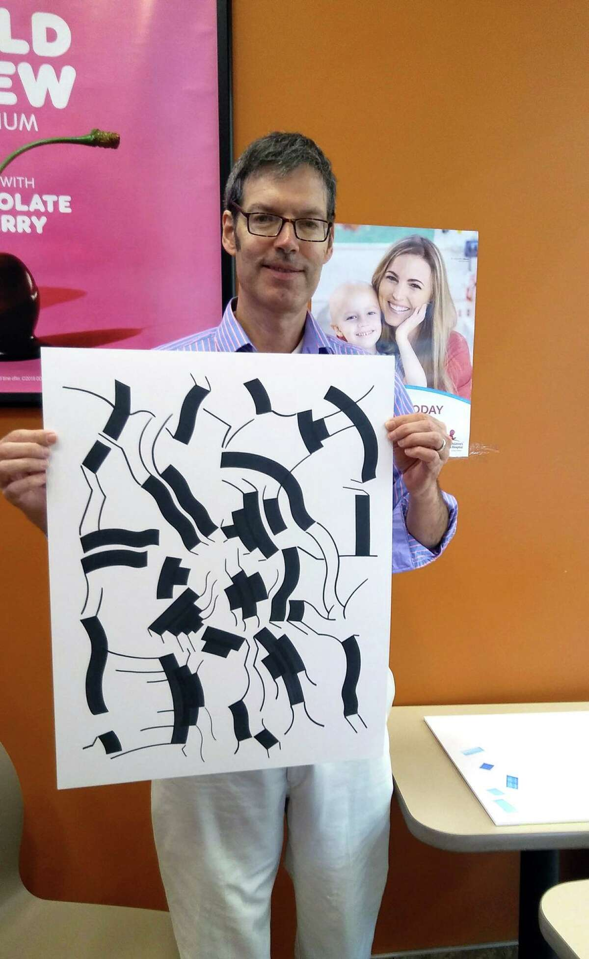 Bob Carley holds his abstract drawing at the Dunkin Donutsat the Walmart on Connecticut Avenue in Norwalk.