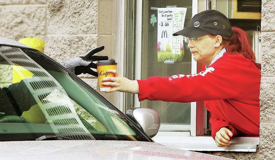 A gloved hand reaches out to accept a coffee at a local McDonald's restaurant's drive-through window. Photo: John Badman | Hearst Newspapers