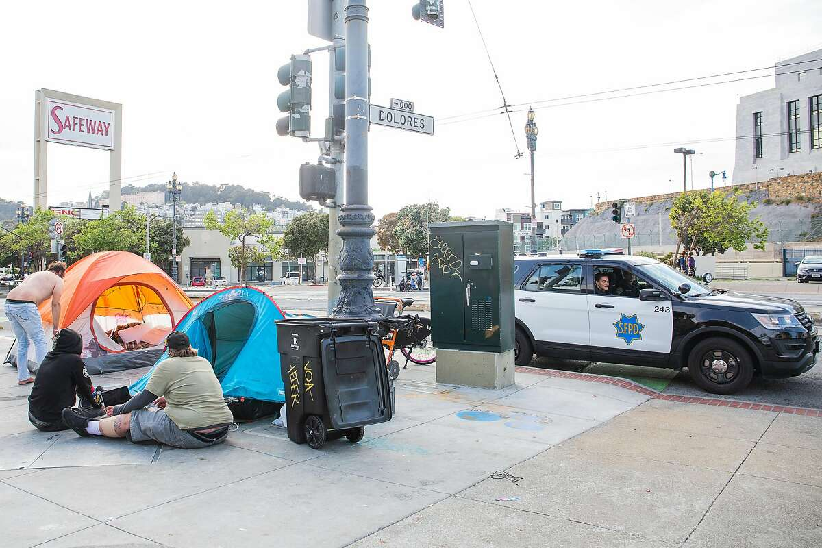 A San Francisco police officer asks a group of people experiencing homelessness to move six feet apart on April 9, 2020 on Dolores and Market Street.