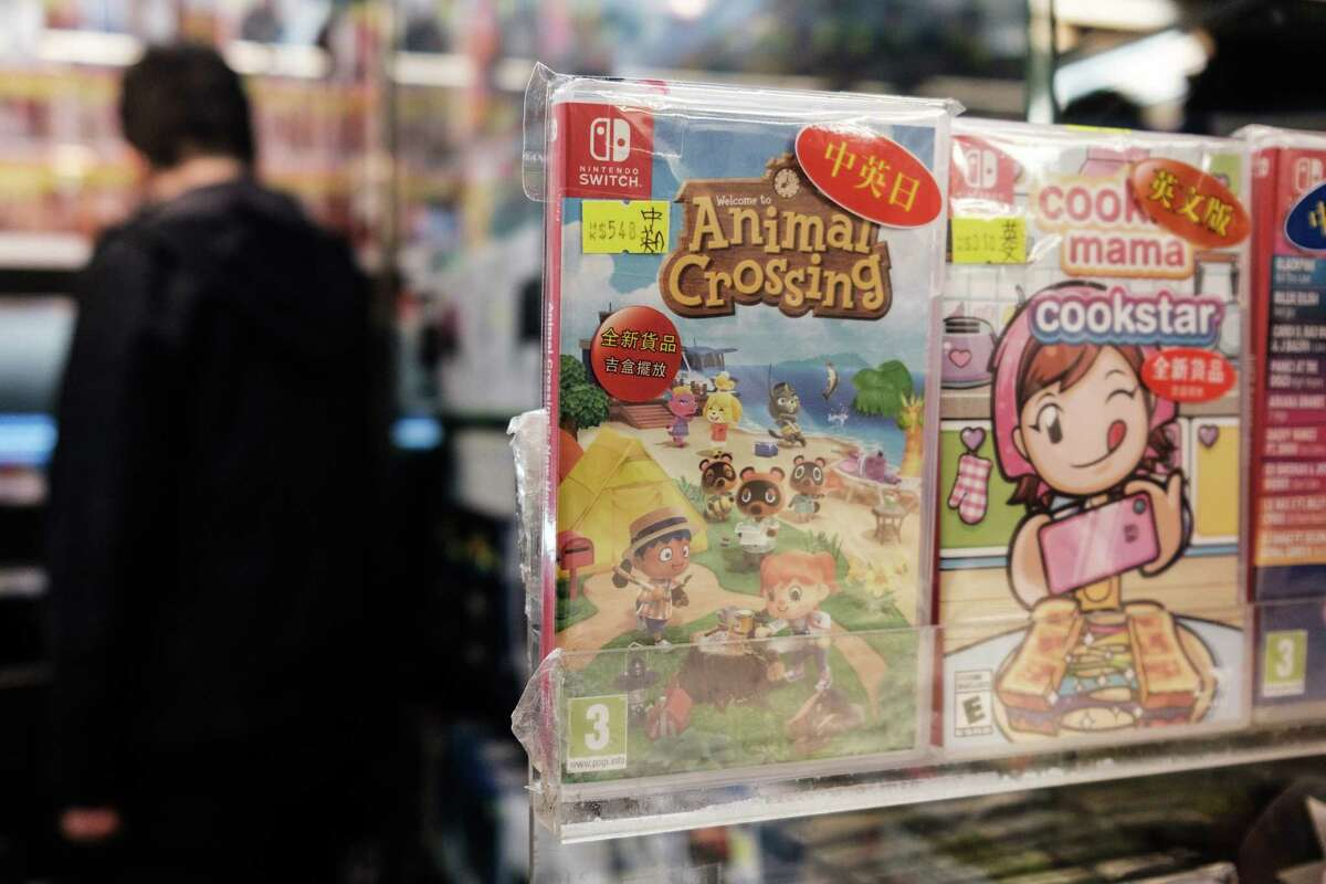 A copy of Nintendo computer game Animal Crossing: New Horizons (C) is displayed in a shopping mall as a customer browses other games in Hong Kong on April 10, 2020.