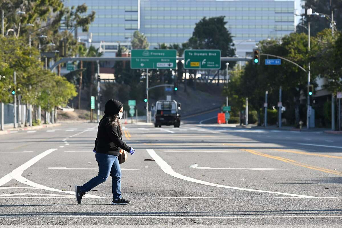 A woman wears a mask as she crosses an empty street near the Los Angeles Convention Center in downtown Los Angeles California March 30, 2020. - The California National Guard is currently setting up the convention center as a field hospital to help lessen the strain on LA-area hospitals during the coronavirus crisis. (Photo by Robyn Beck / AFP) (Photo by ROBYN BECK/AFP via Getty Images)