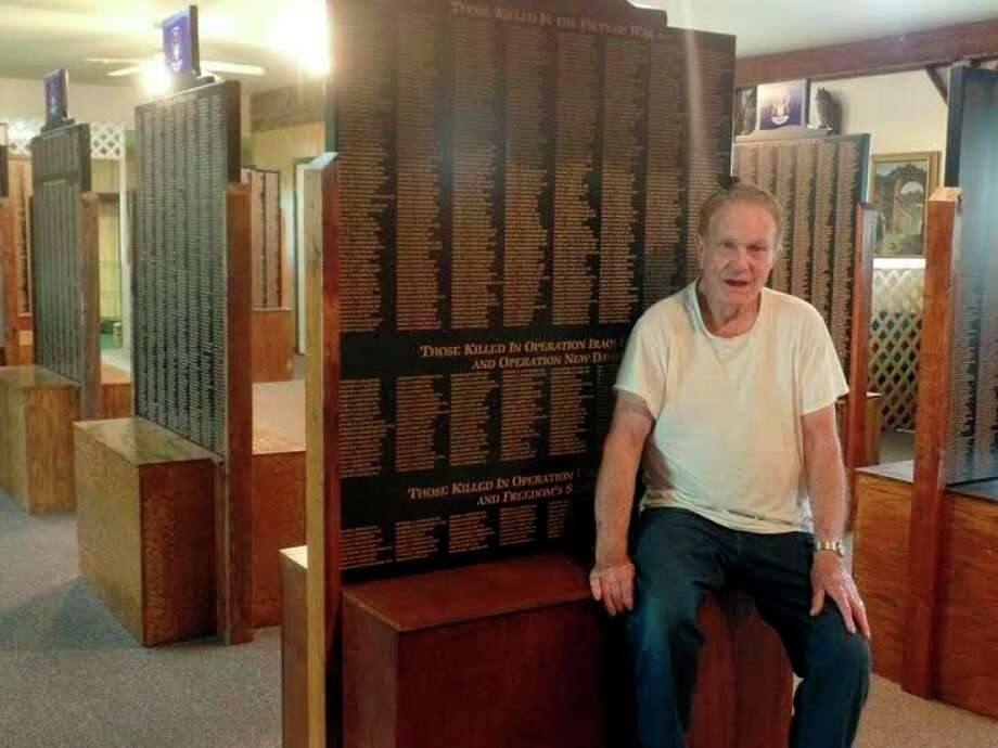 The Farver Road Christian facility also has a Noah's Ark display, and a Veteran Memorial Wall with 20,000 names of deceased Michigan veterans etched on 20 wall panels is housed in one end of the facility. Pastor Duane Plonta sits in front of one of the panels. (Mary Drier/For the Tribune)