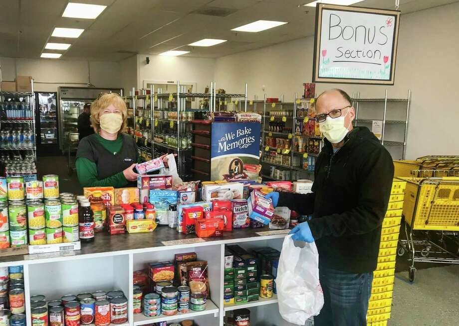 Volunteers Marsha Stamas, left, and Jim Mier, right, place items into bags inside The Bridge Food Center. (Photo provided/Marsha Stamas)