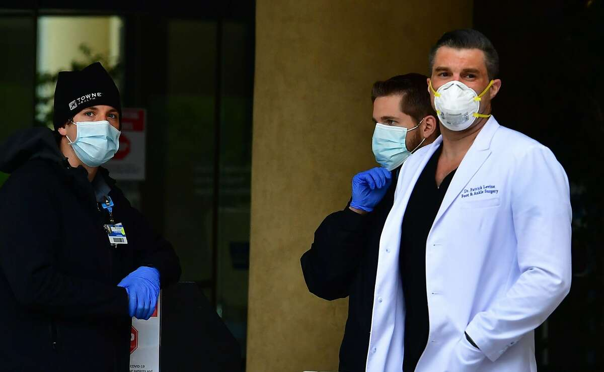 Medical personnel in facemasks are seen outside a hospital in Burbank, California on April 7, 2020, as Los Angeles County officials say the number of coronavirus cases has reached 6,910 with a death toll of 169. (Photo by Frederic J. BROWN / AFP) (Photo by FREDERIC J. BROWN/AFP via Getty Images)