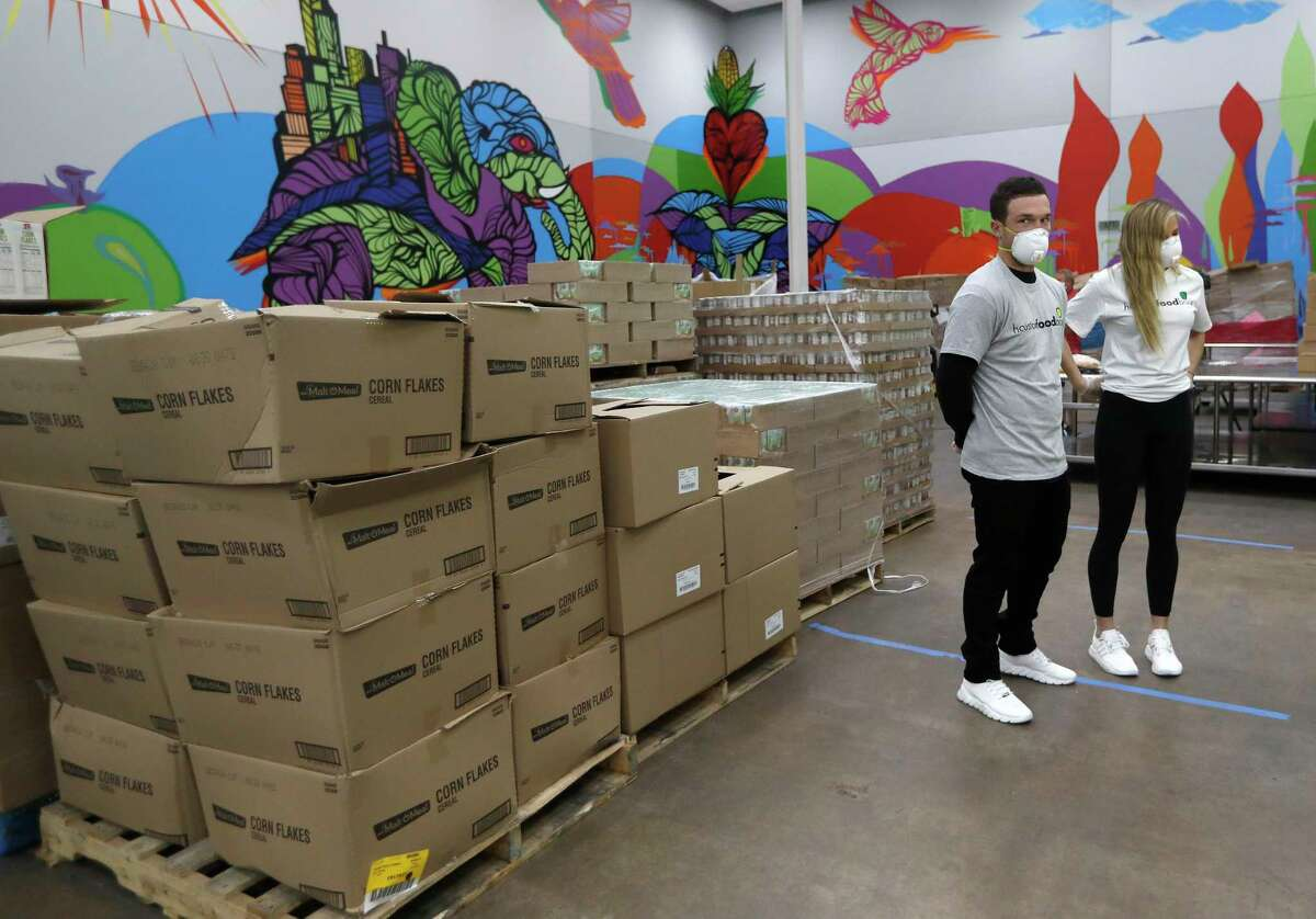 Houston Astros Alex Bregman and his fiancee, Reagan Howard prepare to start packaging sustainable kids meals at the Houston Food Bank, in Houston,Friday, April 10, 2020. Bregman launched his FEEDHOU, a $1 million fundraising campaign to help feed Houston-area residents during the coronavirus pandemic.