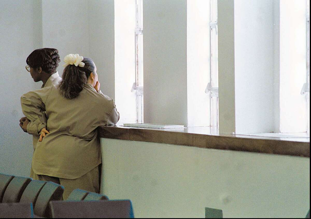 Inmates look out of the window after the conclusion of a visit from the Prisoner Visitation and Support group at a prison.