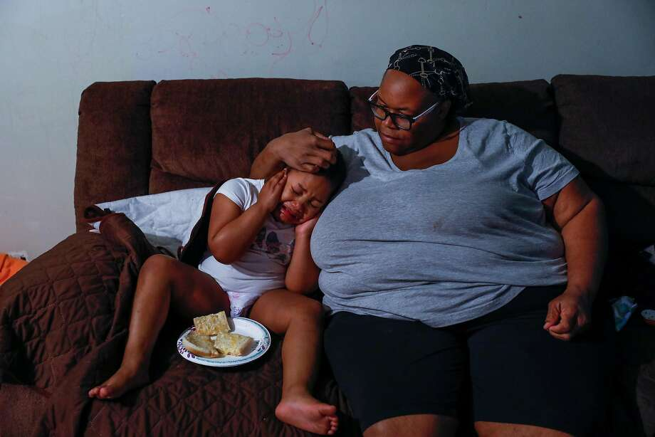 (L-r) Esther Williams consoles her daughter Miracle Smith,4, who is autistic and was upset by the noise of their new washing machine at their apartment on Sunday, April 5, 2020, in Marin City, California. Esther lost her job as a crossing guard supervisor due to Covid-19 and is worried about her finances. She takes care of her two daughters, elderly mother and her niece. Photo: Gabrielle Lurie / The Chronicle
