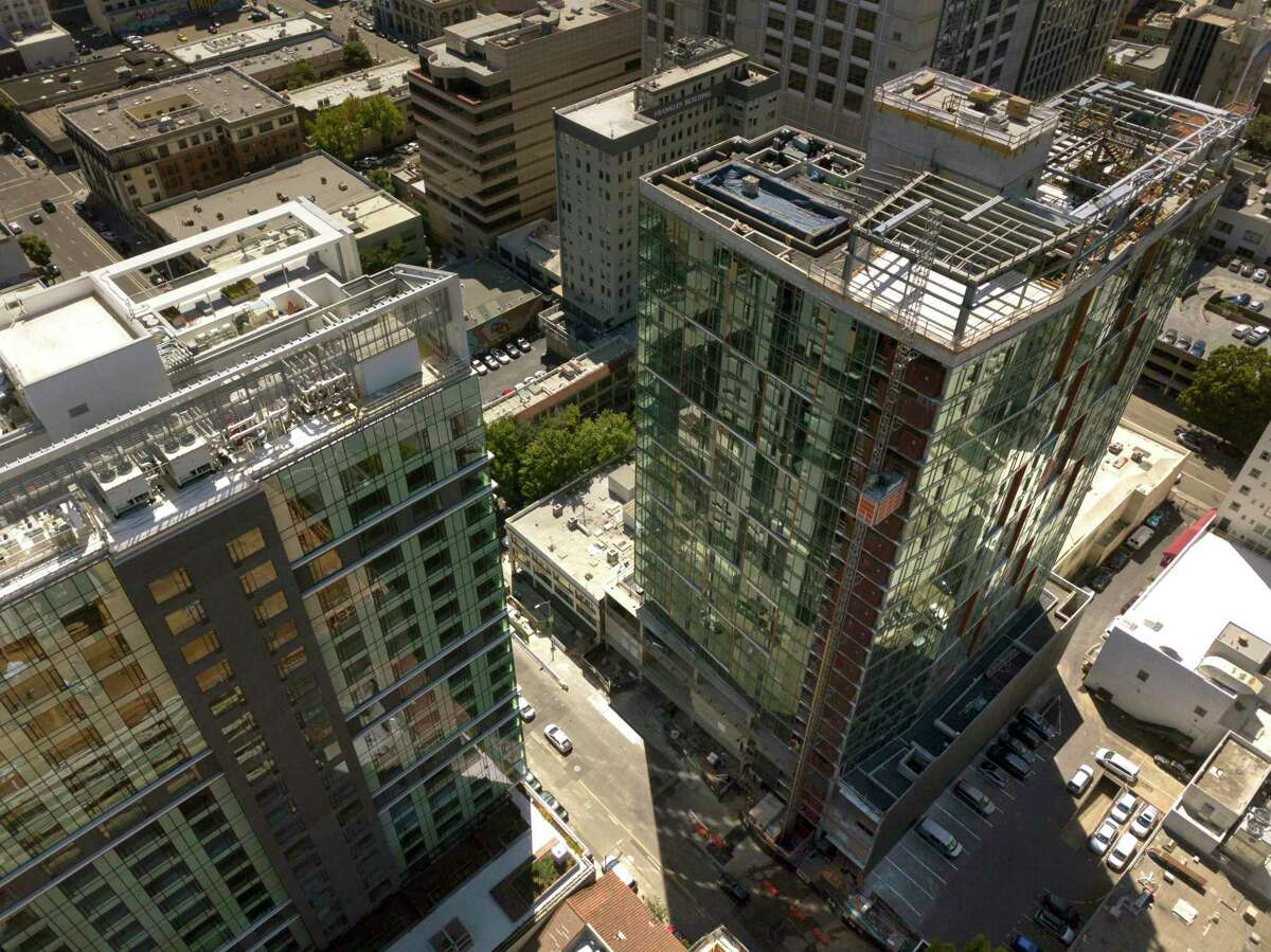 The construction site of a 20-story residential building going up on the 1700 block of Webster Street, lower left, is visible amidst several finished and unfinished construction projects in Oakland Calif., on Wednesday, July 17, 2019. Oakland's downtown has long been revered as hip, electric and historic. Five years ago, the area underwent a transformation minority-owned nail salons shuttered and were instead replaced by hipster bike shops. Now, stores and other businesses are facing a similar transformation as cranes dot the skyline and 20-story buildings go up. One downtown block, near 17th and Webster, is a microcosm of the change that's coming once again to downtown Oakland. There are three big development projects currently under construction on that block - two of which will have 20-story towers.