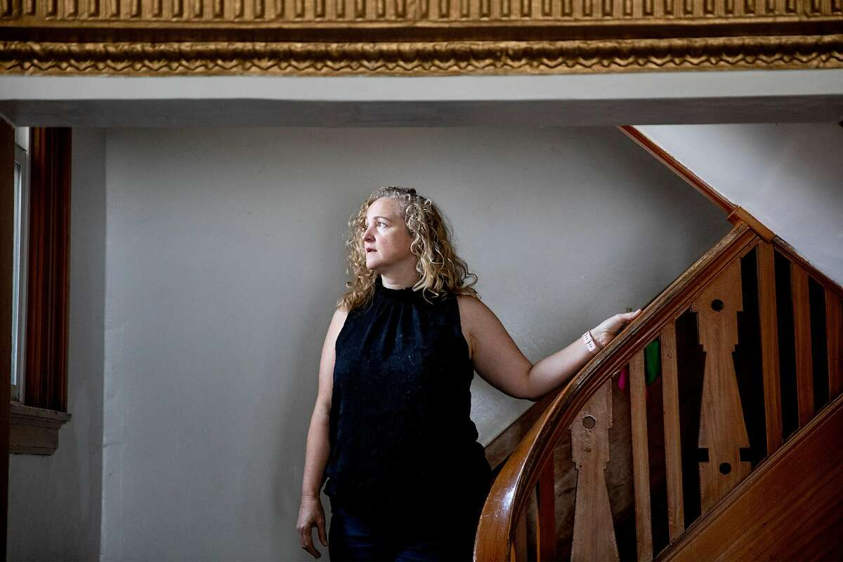 Eliote Durham poses for a portrait in stairway leading to her former neighbor Larry Kaplan's apartment in San Francisco, Calif. Friday, April 10, 2020. It's almost certain the number of COVID-19 cases in San Francisco has been underestimated. Durham believes her neighbor Larry Kaplan, a longtime Yellow Taxi driver, had COVID-19. He had been ill for much of February after picking up a raft of travelers from the airport, and complained of weak lungs and a cough that wouldn't go away. He was found dead during a welfare check in March, and the medical examiner's office is investigating.