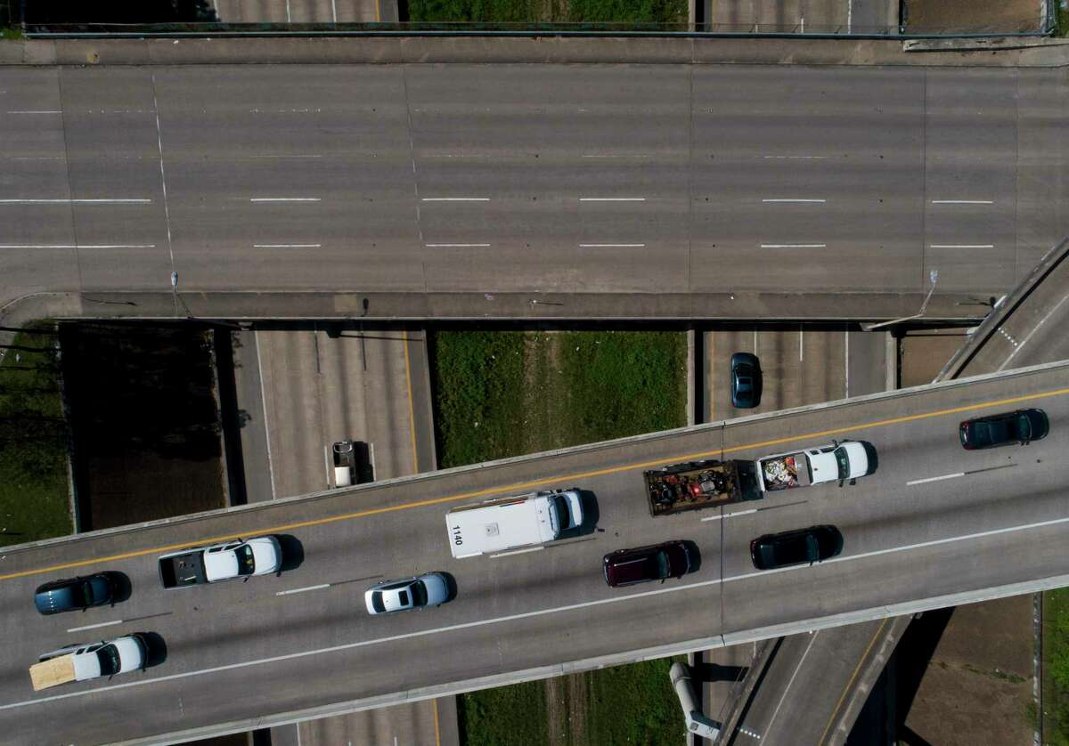 A line of cars and trucks moves from northbound Interstate 45 to Interstate 10 eastbound on March 25, 2020, in Houston. A new study estimates making all vehicles electric could save 148 annually in Houston.