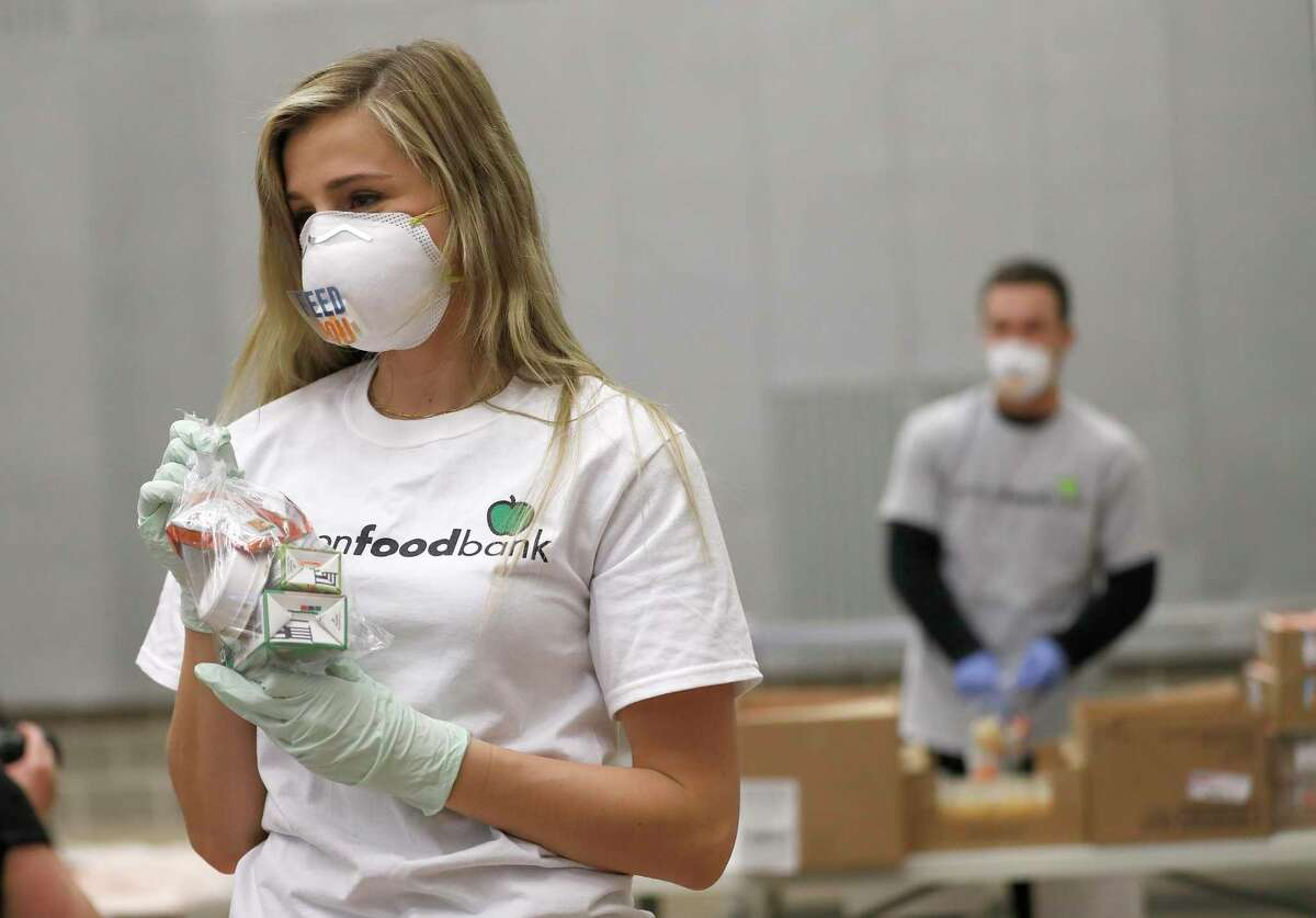 Reagan Bregman packages sustainable kids meals at the Houston Food Bank, in Houston,Friday, April 10, 2020.