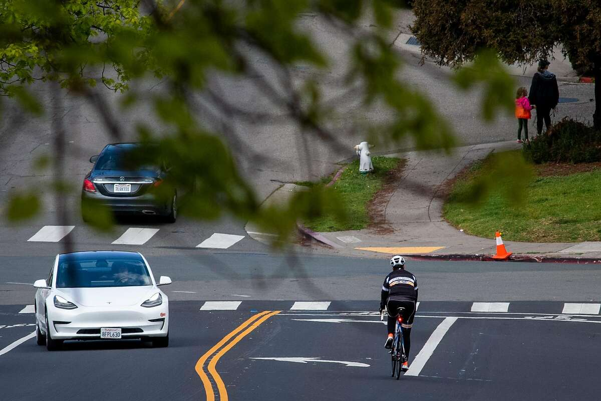 """A cyclist shares the road with vehicles the day before an emergency measure called """"Oakland Slow Streets"""" will shut out automobiles from 74 miles of streets, or about 10% of the roadway space, in Oakland on April 10, 2020 in Oakland, Calif."""