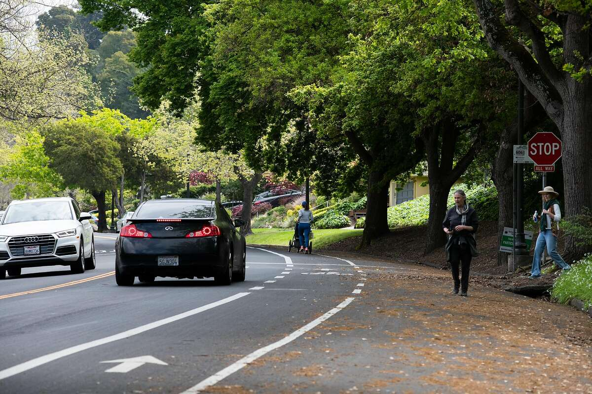 """Pedestrians and joggers share the road with cars the day before an emergency measure called """"Oakland Slow Streets"""" will shut out automobiles from 74 miles of streets, or about 10% of the roadway space, in Oakland on April 10, 2020 in Oakland, Calif."""