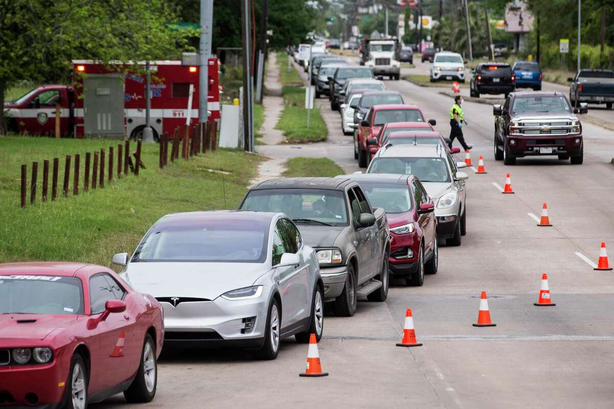 People line up to be tested for coronavirus at a free testing site at Forest Brook Middle School set up by United Memorial Medical Center on Thursday, April 2, 2020 in Houston.