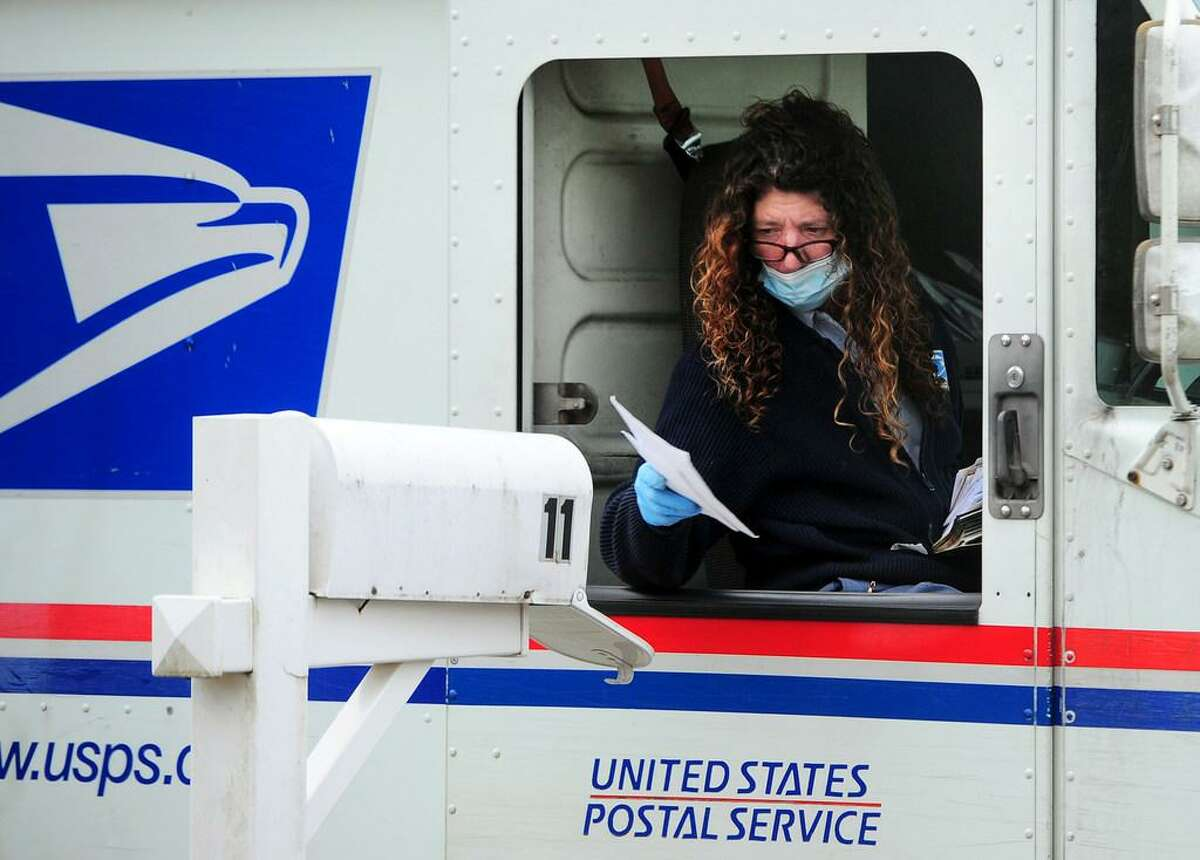 A postal worker wears PPE as she delivers mail in Ansonia, Conn., on Wednesday Apr. 8, 2020.