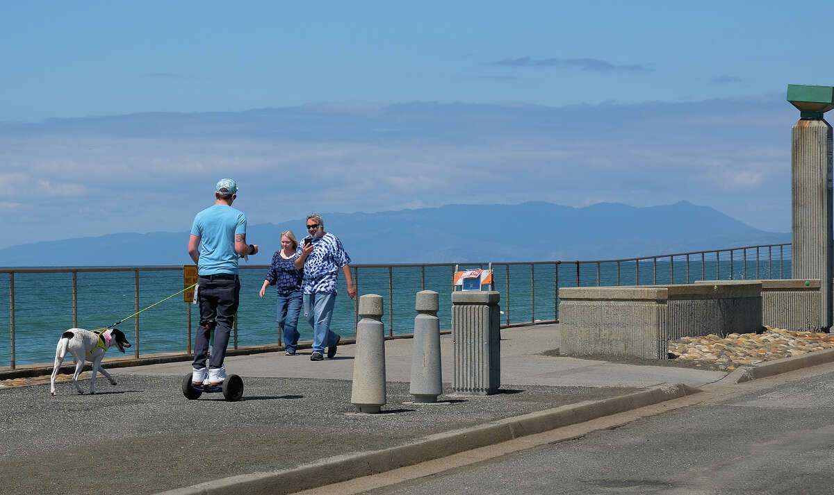 A dog walker on a hoverboard passes a couple on the Pacifica waterfront near the city's famous pier. (Friday, April 10, 2020.)