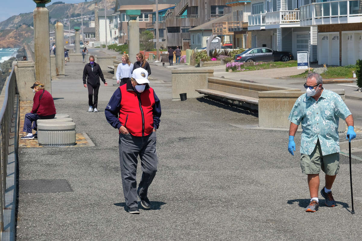 The degree of social distancing to reduce the chance of coronavirus infection varies markedly on the Pacifica waterfront near the city's famous pier. These gentlemen wear masks as they maintain a good 6 feet of separation while conversing. (Friday, April 10, 2020.)