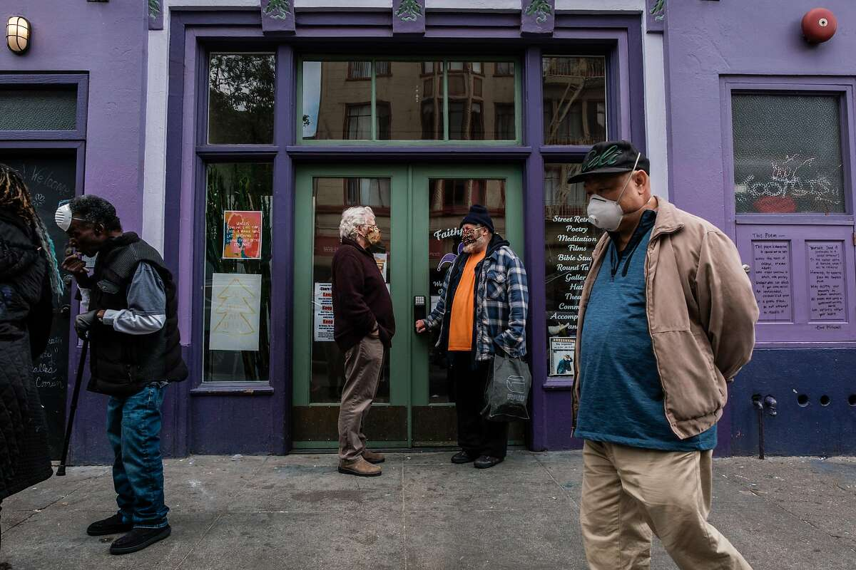 Sam Dennison, co-director of Faithful Fools, speak to Booby Lane near the entrance to Faithful Fools in the Tenderloin in San Francisco, Calif. on Friday April 10, 2020.