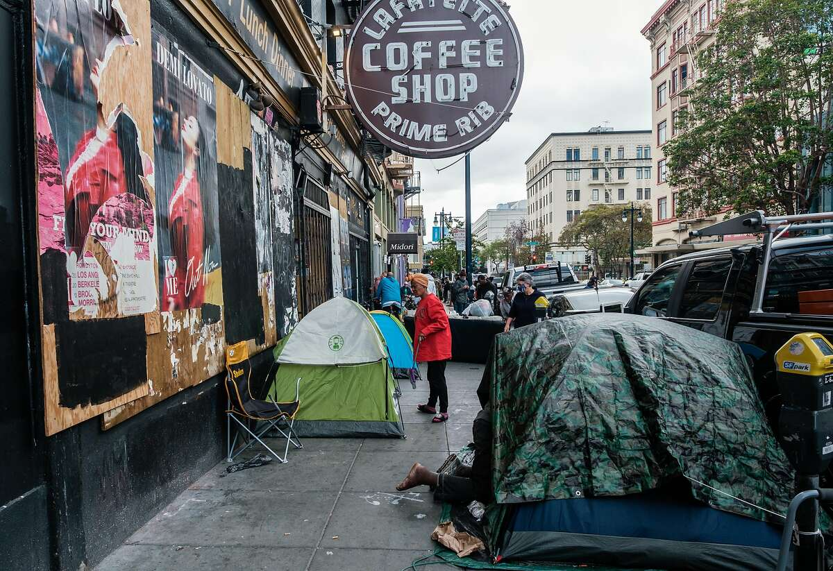 People are seen near a row of tents in the Tenderloin in San Francisco, Calif. on Friday April 10, 2020.