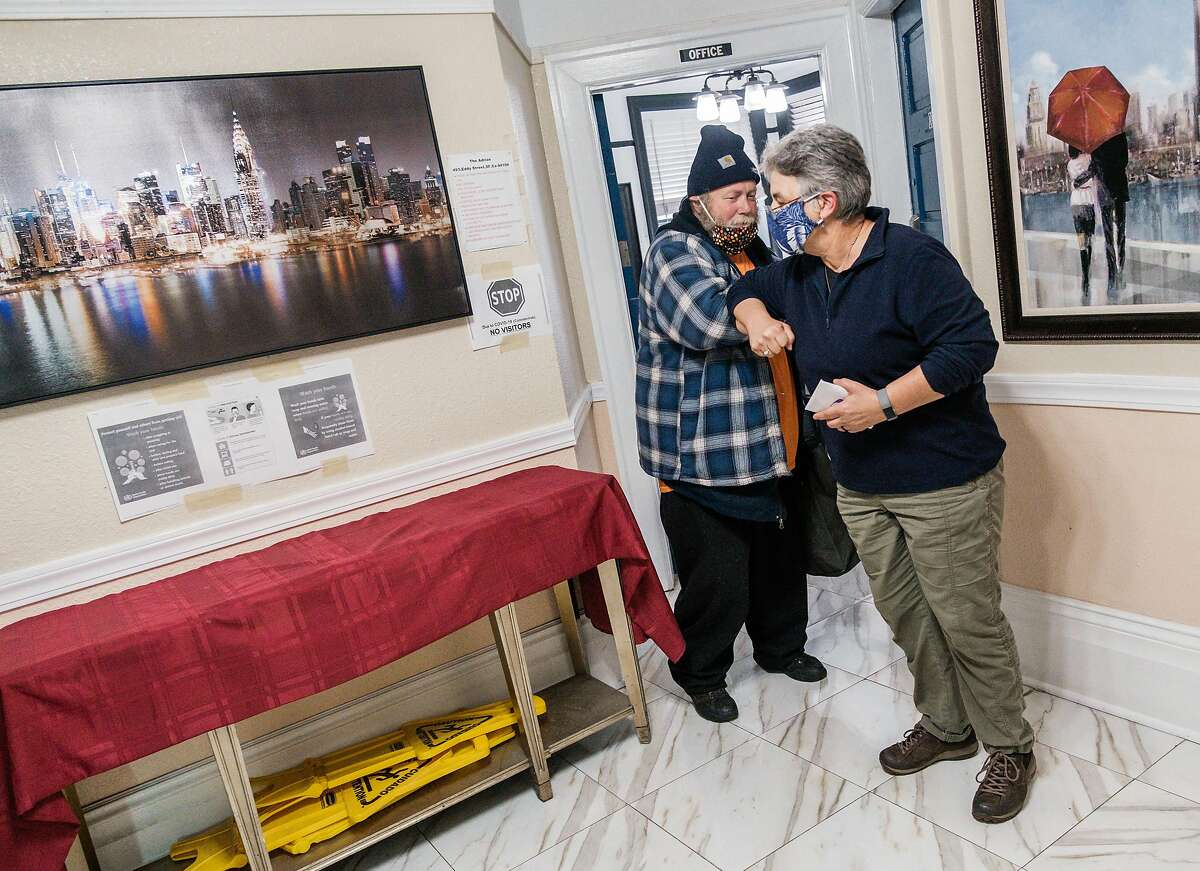 Carmen Barsody, co-director of Faithful Fools, helps Booby Lane get into a hotel room in the Tenderloin in San Francisco, Calif. on Friday April 10, 2020.