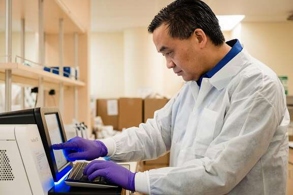 Microbiologist Dr. Charles Chui checks on the newly installed NextSeq 550 which will sequence COVID-19 genomes in San Francisco, Calif. on Friday, March 20, 2020. The infectious disease specialist at UCSF is sequencing the genomes of every case of COVID-19 in the Bay Area that he can get his hands on.