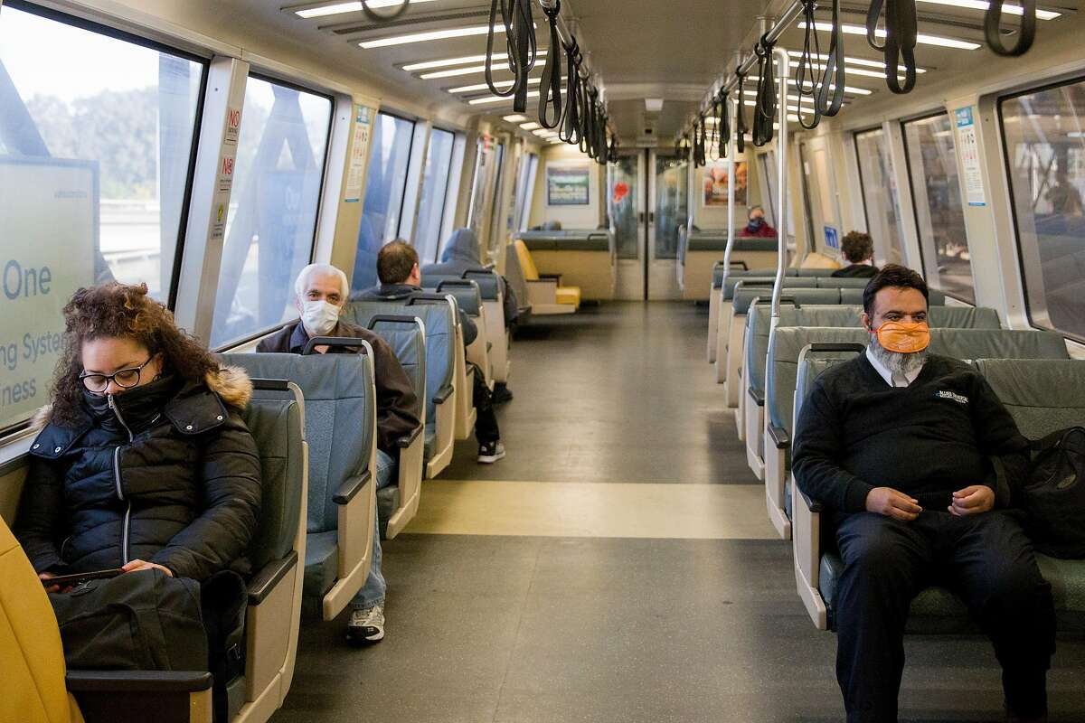 Riders cover their faces with various masks while attempting to socially distance in seats on a San Francisco-bound train leaving MacArthur BART Station in Oakland, Calif. Friday, April 3, 2020.