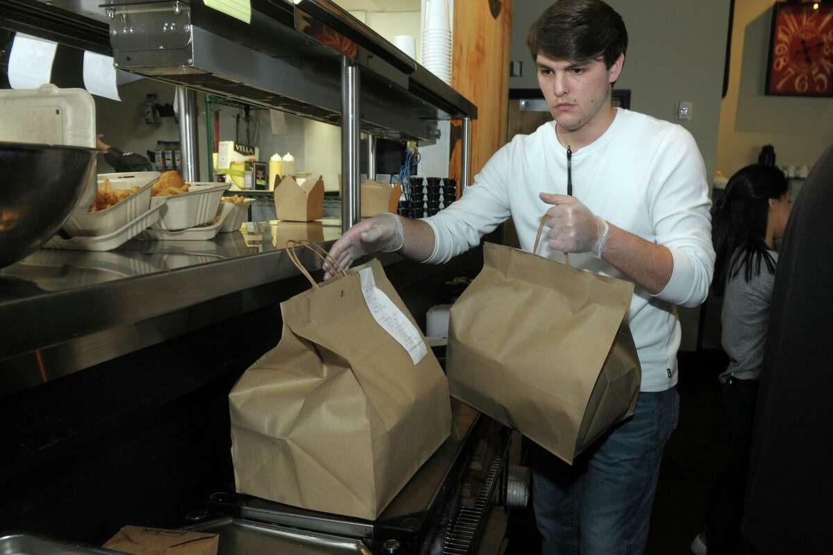 Nick Nistico packages orders for pickup at Sitting Duck Tavern, in Trumbull on Friday. Three Sitting Duck Taverns in Trumbull, Stratford and Oxford have remained open for pickup and online deliveries during the current COVID-19 outbreak.