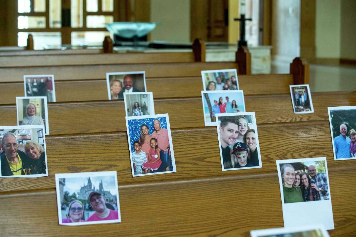 Photos of parishioners are taped to the pews at Christ the Redeemer Catholic Church that will be part of virtual masses at the church on Friday, April 10, 2020 in Houston. The coronavirus pandemic has shut down most religious services throughout the country and many churches are offering services through social media and video conferencing.