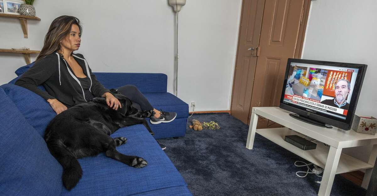 Brazilian foreign correspondent for Folha de São Paulo, Giuliana Miranda, pets Nico, her black Labrador, while watching on TV the news on the pandemic as she works and stays most of the time at home nowadays in her apartment in Alfama neighborhood, due to the COVID-19 Coronavirus emergency, on April 07, 2020 in Lisbon, Portugal. Although the press is exempt from the stay-at-home restriction, most of the media organizations advise their staff to minimize their outings. With 345 deaths and 12.442 confirmed cases, the country is feeling the impact of the COVID-19 Coronavirus, and the Portuguese Parliament approved on April 02 the extension of the state of emergency that, among other things, severely restricts the population's unnecessary movements. (Photo by Horacio Villalobos#Corbis/Corbis via Getty Images)