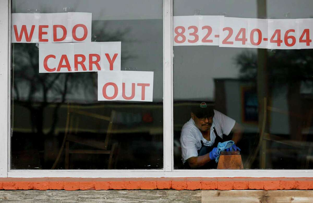 Enrique Torres, co-owner of The Mesquite Grill, wipes down a booth in the dining room which holds a maximum capacity of 120 people, April 6, 2020, in Houston. Torres and his partners had hoped to get a loan through Harris County's previous $10 million small business loan fund for businesses hurt by the coronavirus pandemic.