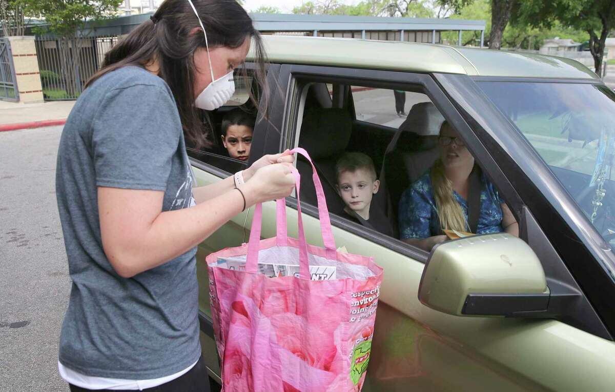 Westwood Terrace Elementary administrative intern Stephanie Janick hands over a package of items Wednesday to be given to parent Chelsea Henry for her son, Zander Sanchez (seated in the back of the car), who attends the school . Schools are in the second or third week of remote learning but large numbers of students are missing. Northside ISD reports 18 percent haven't checked in with all of their teachers.