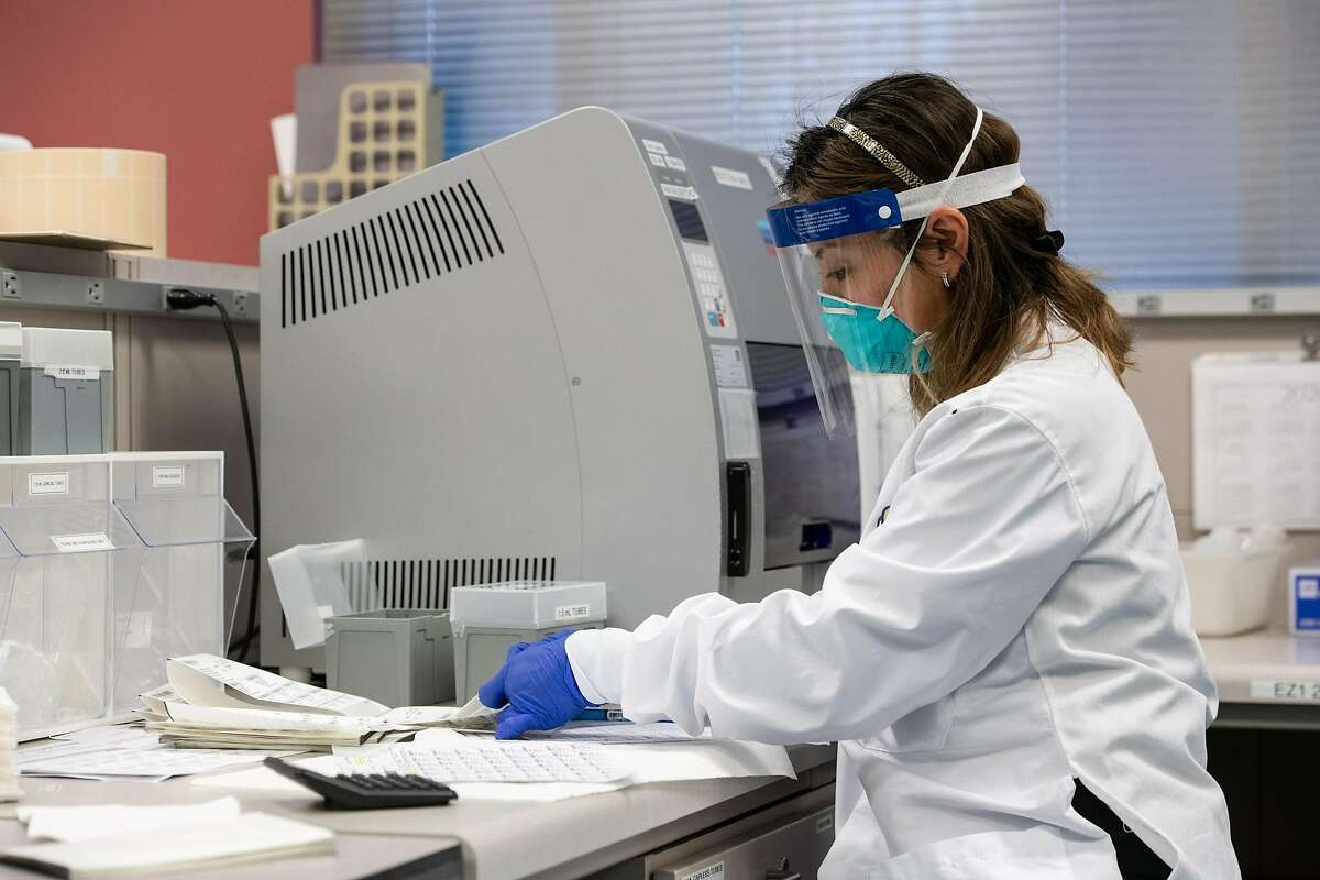 Medical researchers perform serology - testing blood samples to find out whether someone already had and recovered from COVID-19 - in Stanford University's Clinical Virology Lab.