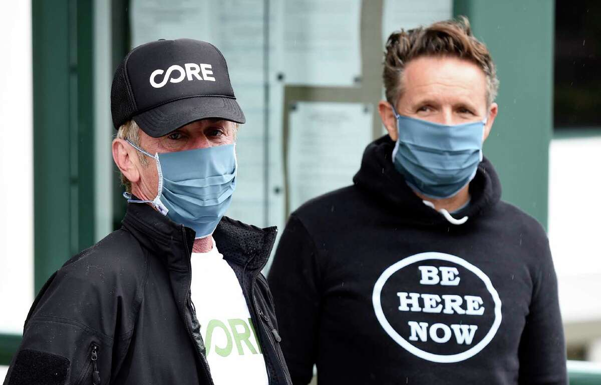 In this April 9, 2020 photo, actor Sean Penn, left, founder of the nonprofit organization Community Organized Relief Effort (CORE), and MGM Worldwide Television Group chairman Mark Burnett wear masks as they visit a CORE coronavirus testing site at Malibu City Hall in Malibu, Calif. The Oscar winner's disaster relief organization called CORE has teamed up with Los Angeles Mayor Eric Garcettia€™s office and the citya€™s fire department to safely distribute free drive-through COVID-19 test sites for those with qualifying symptoms.(AP Photo/Chris Pizzello)