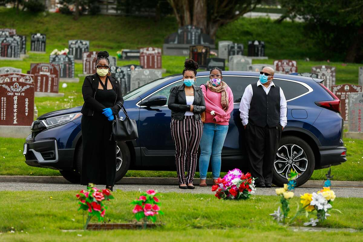 (L-r) Debra Holloway, Rashawn Henry, Raneisha Henry, and Robert Henry watch from the car as their mother and grandmother Tessie Henry who died of Covid-19 at the age of 83 is buried on Wednesday, April 8, 2020 in Colma, California.