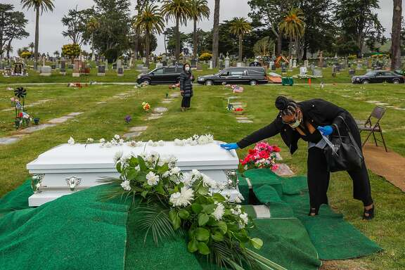 Debra Holloway prays over her mother Tessie Henry�s casket before saying goodbye to her after Covid-19 at the age of 83 is buried on Wednesday, April 8, 2020 in Colma, California.