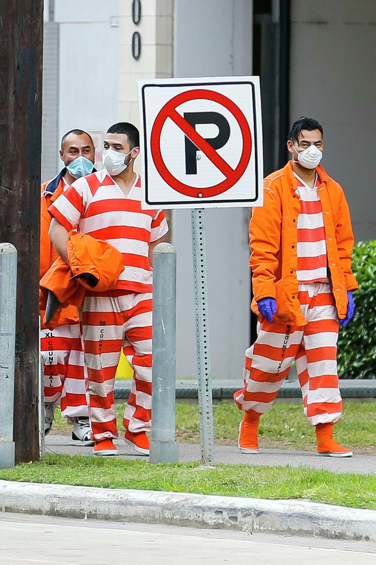 Harris County Jail inmates wear masks as they walk between buildings in the area of the jail, Friday, April 3, 2020, in downtown Houston.