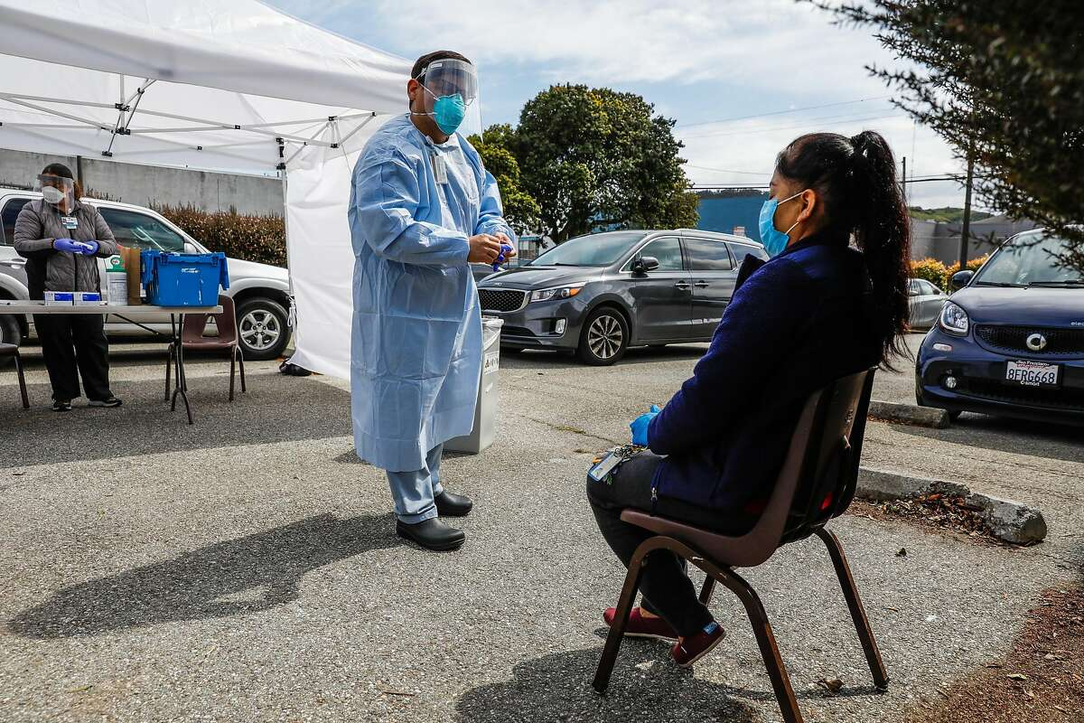 Dentist Dr. Marco Reyes (center) talks to patient Angela Rios (right) after giving her a Covid-19 test in San Francisco, California on Thursday, April 9, 2020. A small tent in the Southeast Health Center parking lot was serving as an alternative testing site for potential COVID-19 cases. Patients who are tested have been pre-screened by a health care provider.