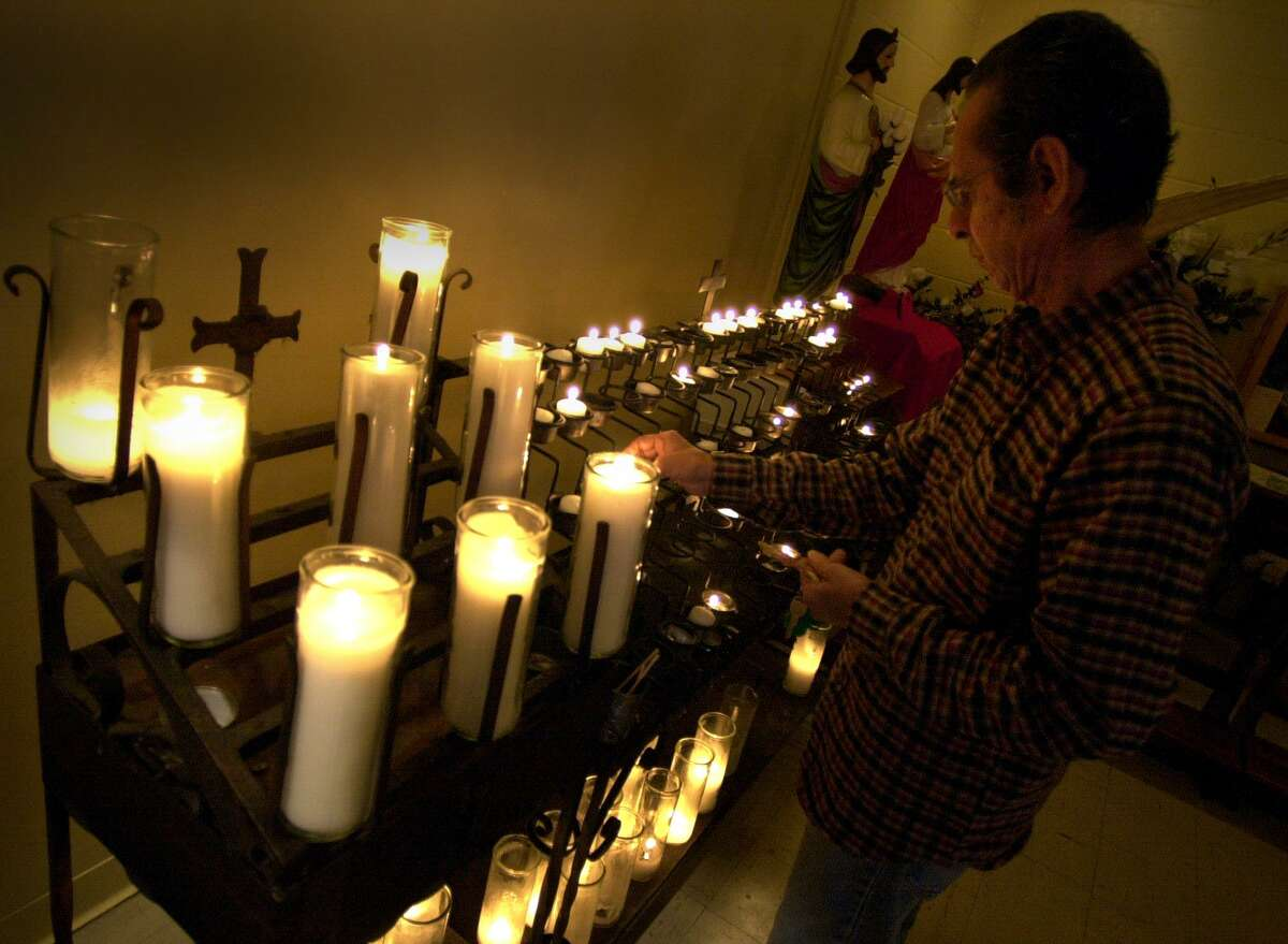 Religion/ Parker: Ramiro Castro lights candles at Sacred Heart Catholic Church Sunday. The church offers Mass in Spanish and is often crowded. Castro has been going to church at Sacred Heart since 1954. John Davenport / Staff