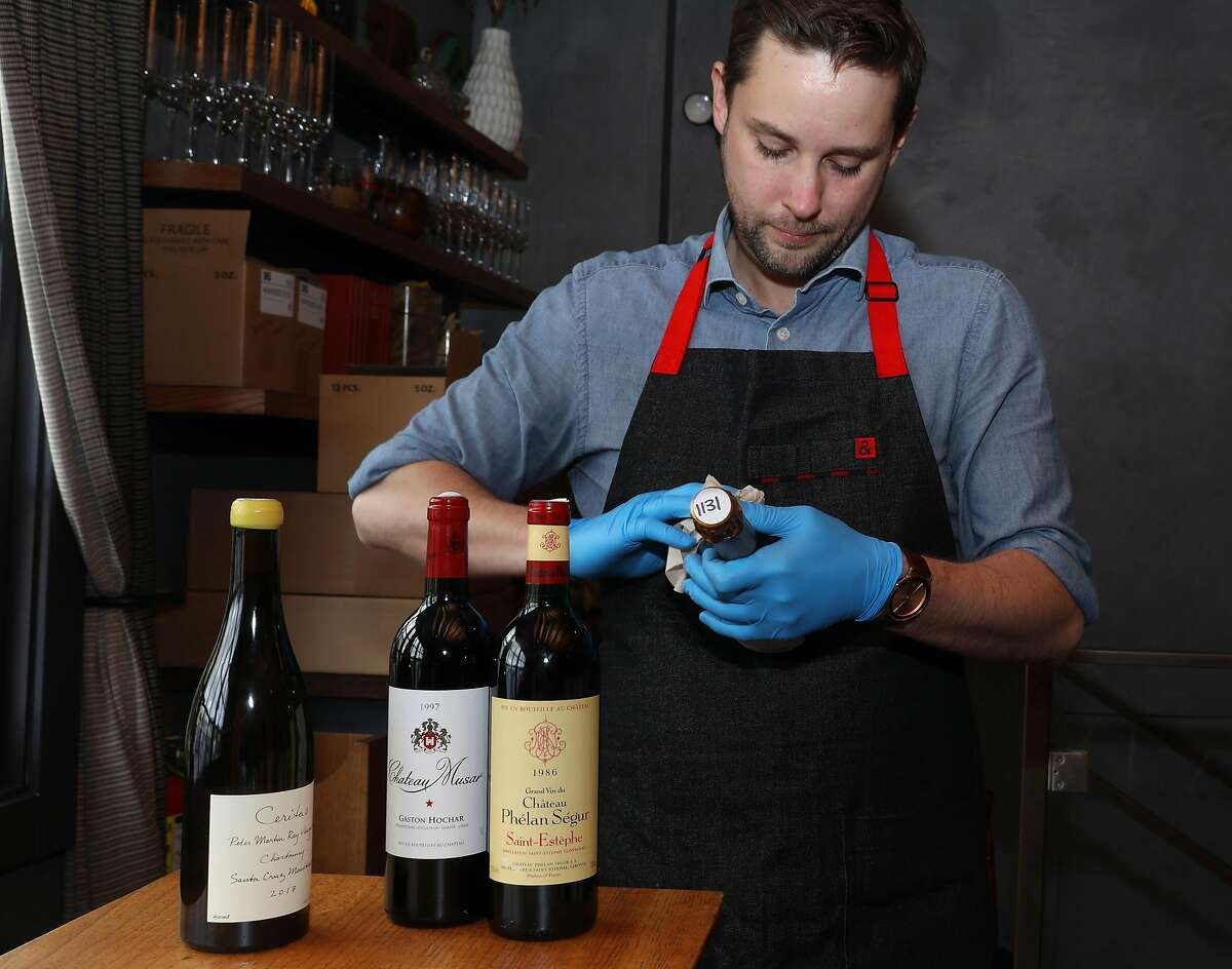 """Beverage director Matt Dulle checks bottles of wine at Lazy Bear restaurant on Thursday, April 9, 2020, in San Francisco, Calif. Lazy Bear restaurant in the Mission has reconfigured its restaurant to be a """"commissary,"""" kind of like a general store, where customers can come shop for provisions and pick up bottles of wine, including some rare wines from Lazy Bear's cellar."""