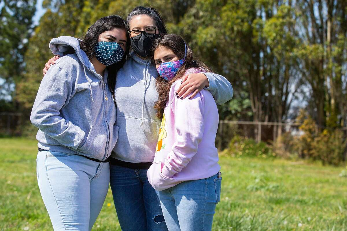 A portrait of Clarissa Rivera-Loo (center) with her daughters Alandra Martinez (left) and Ava Martines, 11, on Friday, April 10, 2020, in San Francisco, Calif. Rivera-LooÍs husband Ken Loo has COVID-19. His condition has improved, but he remains in quarantine at a hotel in Burlingame because he keeps testing positive for the coronavirus.