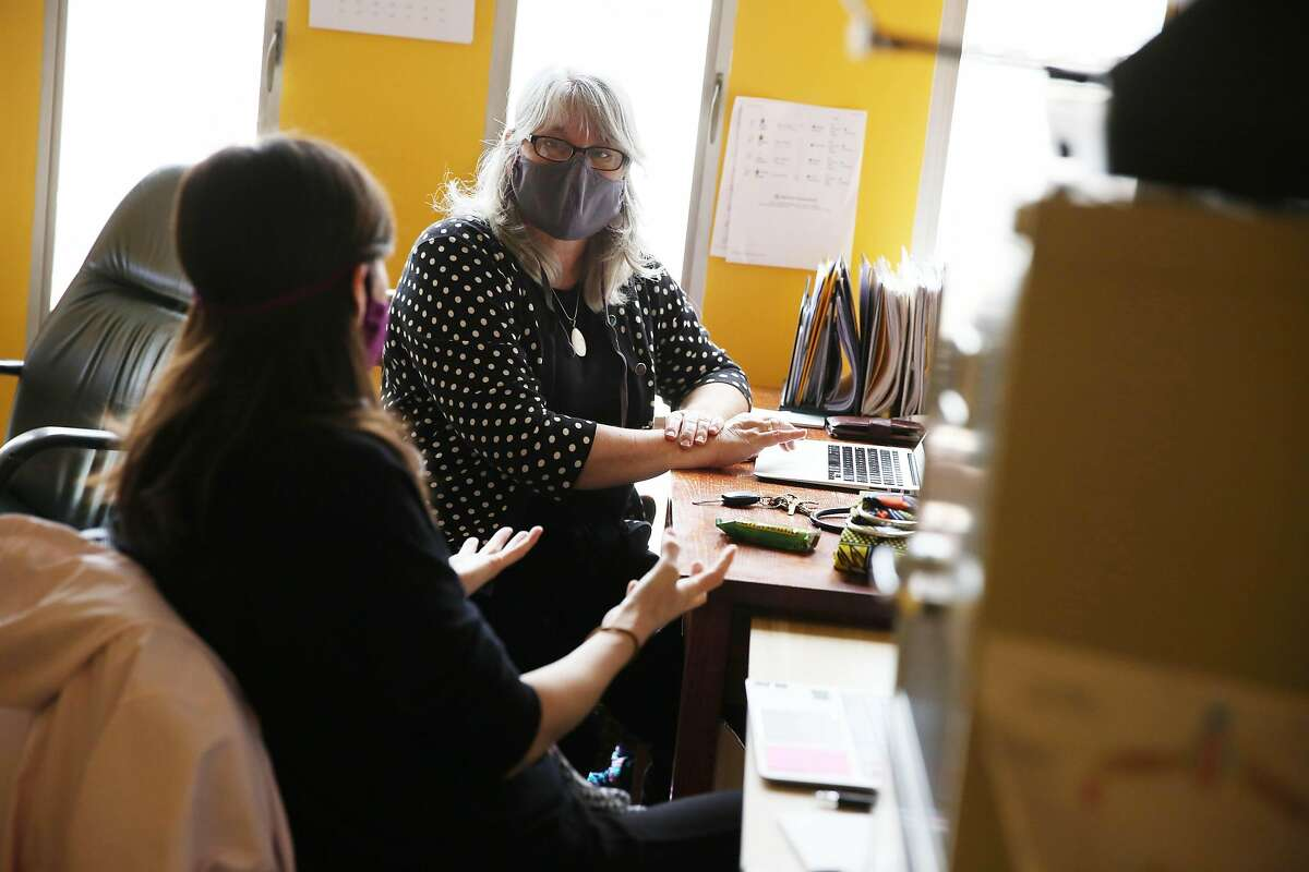Nancy Myrick (right), director San Francisco Birth Center, and Kelly Wong McGrath (left), midwife, wear masks as they work in an office at the San Francisco Birth Center on Monday, April 6, 2020 in San Francisco, CA.